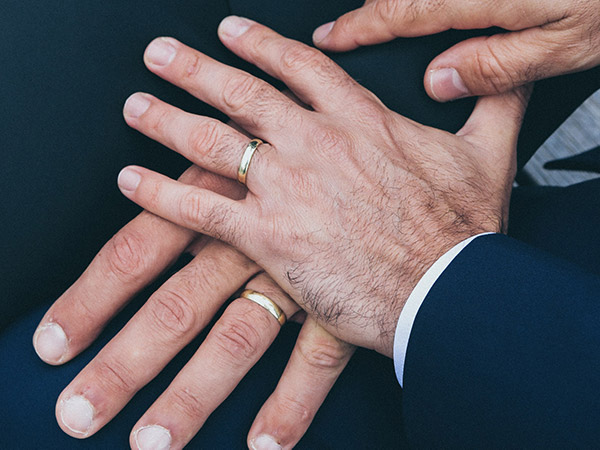 two-men-holding-hands-wedding-rings